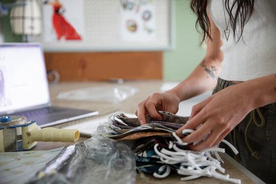 Close up young e-commerce seamstress making COVID-19 face masks