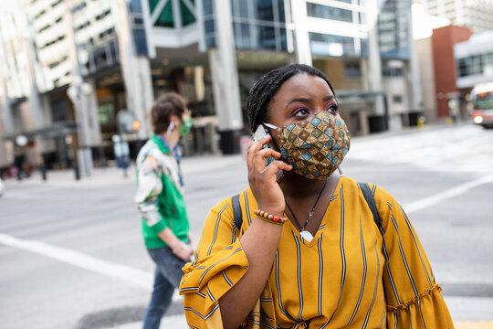 Teenage girl in face mask talking on smart phone on city street corner