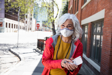 Portrait happy senior woman in face mask with smart phone on sidewalk