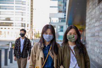 Portrait happy sisters in face masks walking on city sidewalk