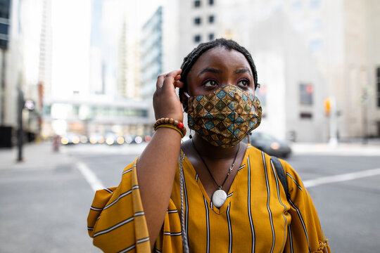 Young woman in face mask on city street