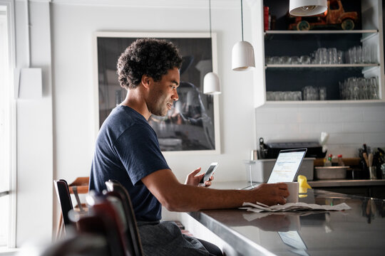 Male business owner working at laptop in restaurant