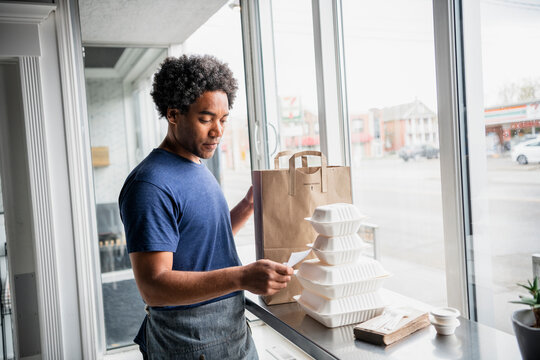 Male business owner preparing takeout orders at cafe window