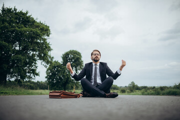 Handsome businessman in black suit and eyeglasses sitting in lotus pose in middle of road. Bearded man trying to reduce stress at work during meditation.