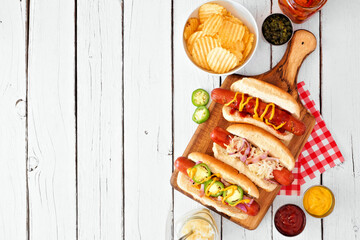 Variety of BBQ hot dogs. Above view table scene side border over a white wood background. Copy...