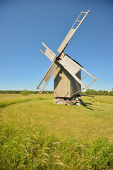 An old wooden windmill on the field against clear blue sky on a clear summer day.  Saaremaa,...