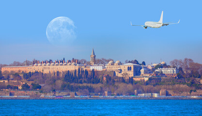 """Airplane flying above the Topkapi palace with white moon - Istanbul, Turkey """"Elements of this image furnished by NASA """""""