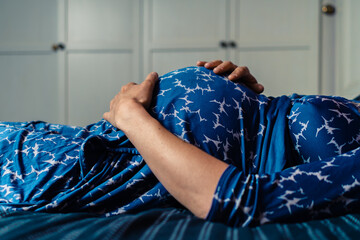 Pregnant woman in gown lying on bed with hand on her belly