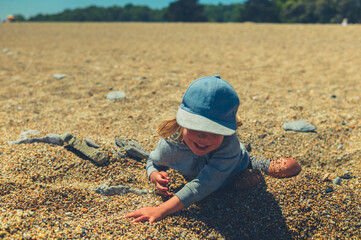 Preschooler boy playing in the pebbles on the beach