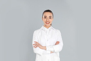 Happy young woman in lab coat on light grey background