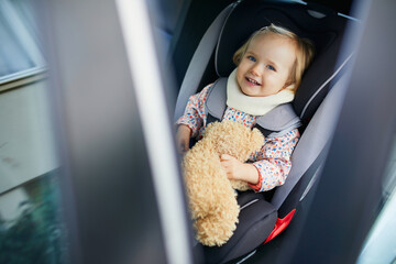 Adorable toddler girl in modern car seat with her favorite stuffed toy