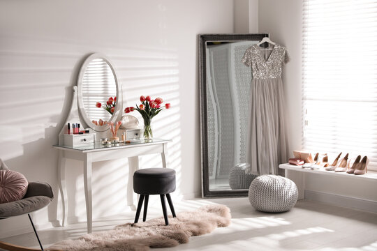 Stylish room interior with elegant dressing table and mirror
