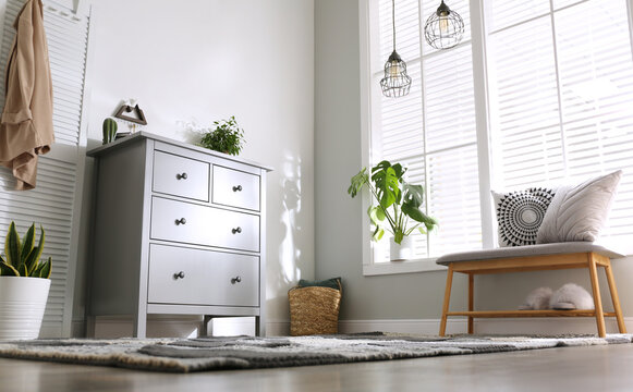 Grey chest of drawers in stylish room interior, low angle view