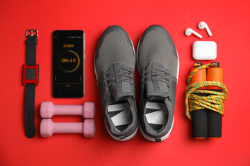 Smartphone with timer and fitness accessories on red background, flat lay