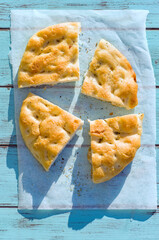Top view, of Ligurian focaccia, cut in slices with rosemary, extra virgin olive oil and salt flakes over a delicate blue wooden board.