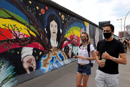 Tourists from France wear face masks as they walk past the East Side Gallery in Berlin