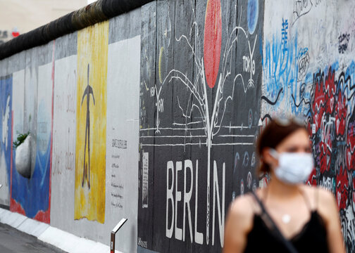 Tourists wear face masks as they walk past the East Side Gallery in Berlin