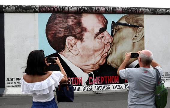 Tourists are seen in front of a graffiti at the East Side Gallery in Berlin