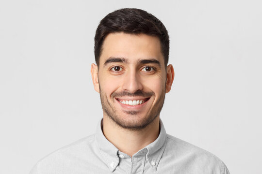 Headshot portrait of young smiling handsome man wearing gray shirt, isolated on studio background