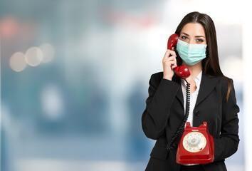 Masked businesswoman using a vintage telephone during coronavirus pandemic