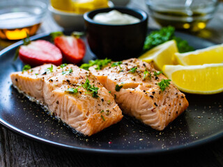 Steamed salmon steaks with lemon, strawberries and creamy dip served on black plate on wooden table