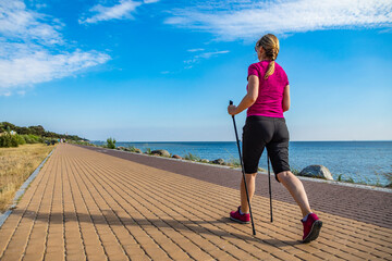 Nordic walking - middle-aged woman training by the sea shore