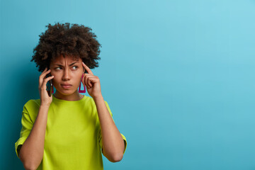 Serious strict woman has telephone conversation, keeps cellular near ear, keeps index finger on...