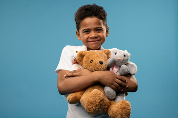 Happy little boy with two soft toys and teddybear smiling at you while playing