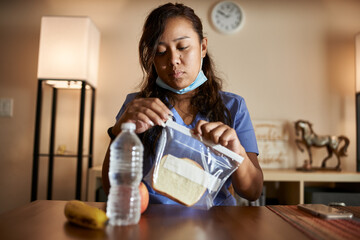 asian filipina nurse at home packing lunch for work