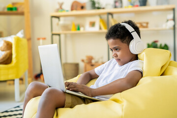 Concentrated adorable schoolkid in headphones looking at laptop display