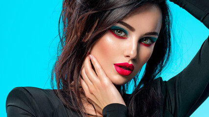 Portrait of beautiful young woman with bright blue makeup.  Pretty girl with long black hair....