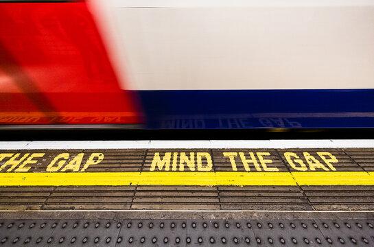 London, UK:   mind the gap tube station sign