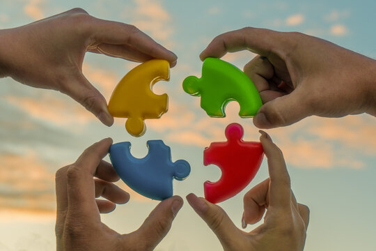 Four hands of businessmen connect colored pieces of the puzzle into a single whole. Business concept idea, partnership, cooperation, teamwork, creative, innovation