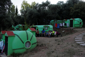 """Members of a family rest at """"Villa Sandia"""", a glam-style camping with pottery """"tents"""" in the shape of watermelons and cucumbers, in Jimera de Libar"""