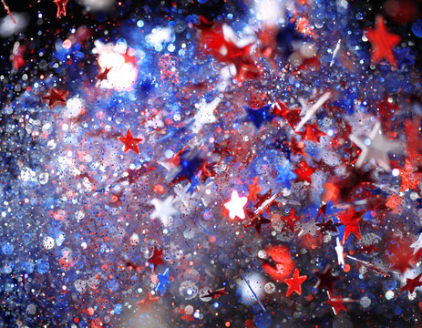 Background of red, white, and blue sparkling glitter scattered with shiny stars confetti. 4th of July celebration background.