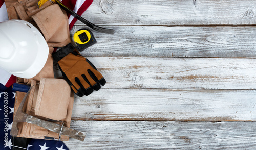USA Happy Labor Day concept with national flag and pouch containing industrial work tools on white rustic wooden background