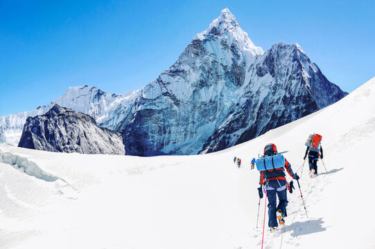 Group of climbers reaching the Everest summit in Nepal. Team work concept.
