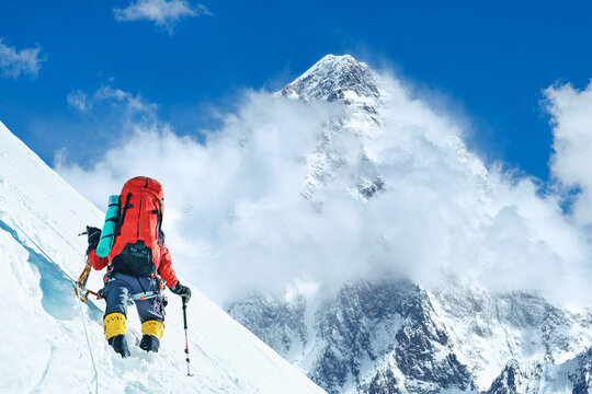 Climber reaches the summit of mountain peak. National Park, Nepal.