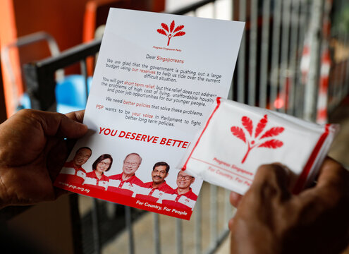 A resident reads a Progress Singapore Party (PSP) leaflet handed out to him at a food centre ahead of the general election in Singapore