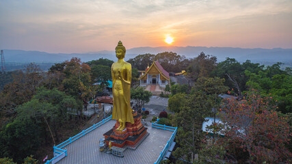 .aerial view sunset at Wat Phra That Jom Wae or Black Scorpion Temple on the high mountain in Chaing Rai Thailand