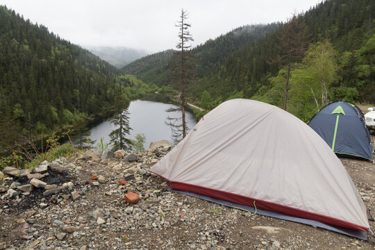 Two small tourist tents by a lake surrounded by mountains with coniferous forest