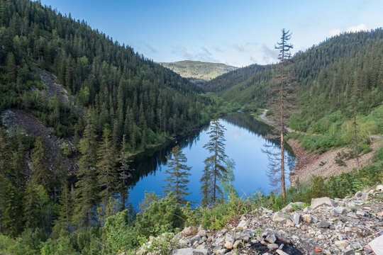 Landscape with a beautiful mountain lake among the mountains covered with coniferous and deciduous trees.