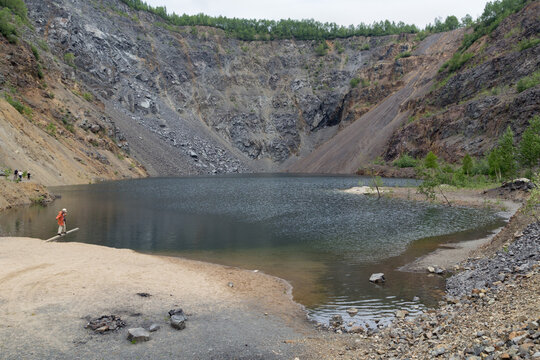 Artificially formed lake in a quarry for stone mining. A girl playing near the lake