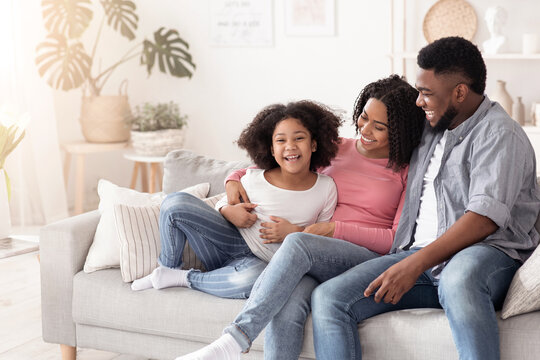 Happy african family, mother father and daughter having fun at home together