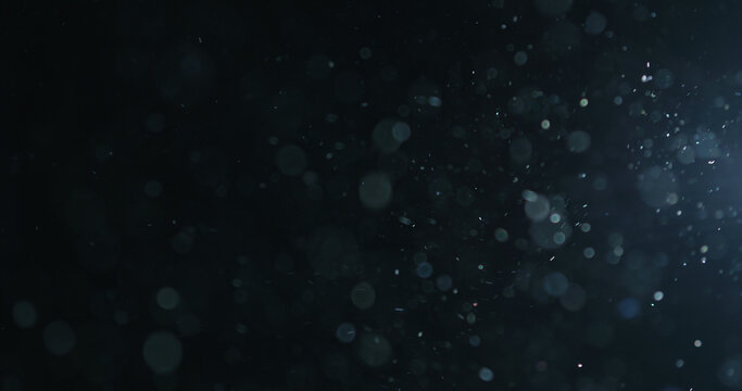 natural dust particles float in air on black background