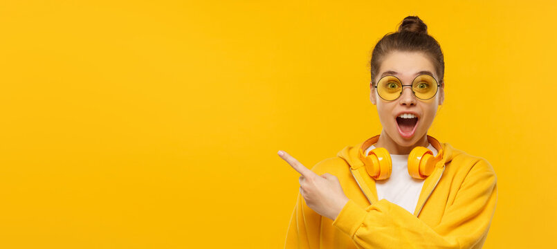 Horizontal banner of young shocked girl, wearing round glasses and headphones on neck, pointing left to copy space, isolated on yellow background