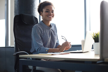 Beautiful young african american woman is sitting in the office and looking at camera.