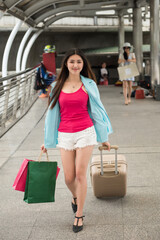 girl hold luggage and shopping bags