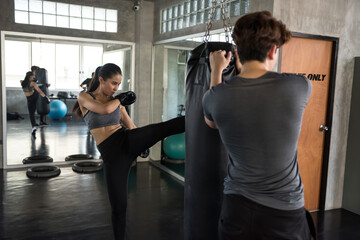 woman kick boxing sandbag with coach in gym