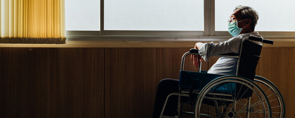 Retirement concept. Panoramic asian elderly man wear mask sitting in wheelchair while looking out...